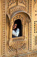 An Indian boy looks out a hand carved sandstone WINDOW in the MAHARAJA'S PALACE located inside JAISALMER FORT - RAJASTHAN, INDIA