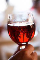 A hand holding a glass of Kir aperitif bright red translucent, in a restaurant, the table, room and lunch guests are reflected upside down in the glass, made by mixing white wine, traditionally Burgundy Aligote, with black currant (called cassis in French) liqueur Cassis Cote d'Azur Var France Bouches du Rhone