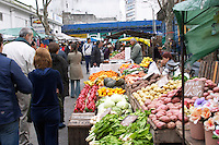 A market stall street market merchant selling vegetables, mangold, chard, blette, potatoes, oranges, bell peppers, pumpkins, people shopping and more market stalls Montevideo, Uruguay, South America
