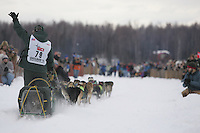 With a dog in a kennel behind him, Jeff King waves to the crowd as he leaves the Willow Restart.  2005 Iditarod Sled Dog Race