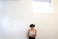 Una modella controlla il suo cellulare in attesa di prepararsi per la presentazione della collezione Autunno Inverno 2014-2015 di Sarli Couture durante la rassegna Altaroma, a Roma, 12 luglio 2014.<br /> A model uses her mobile phone as she waits to prepare for the presentation of Sarli Couture's Autumn Winter 2014-2015 collection at the Altaroma fashion week in Rome, 12 July 2014.<br /> UPDATE IMAGES PRESS/Riccardo De Luca