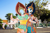 """Thailand. Bangkok. A pair of dummies ( a man and a woman dancing) to be used by tourists for photo session at Wat Arun temple. Wat Arun, also called Temple of the Dawn is a Buddhist temple on the west bank of the Chao Phraya River. The full name of the temple is Wat Arunratchawararam Ratchaworamahavihara. The outstanding feature of Wat Arun is its central prang (Khmer-style tower). Steep steps lead to the two terraces. The height is reported by different sources as between 66,80 m and 86 m. The corners are surrounded by 4 smaller satellite prangs. The prangs are decorated by seashells and bits of porcelain which had previously been used as ballast by boats coming to Bangkok from China. The central prang is topped with a seven-pronged trident, referred as the """"trident of Shiva"""". Around the base of the prangs are various figures of ancient Chinese soldiers and animals. Tha Tian's community is located in the downtown area and in the center of the urban historic district, called Koh Rattanakosin. The Tha Thian is surrounded by a major heritage and tourist site, Wat Arun. 27.03.09  © 2009 Didier Ruef"""