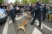 Gegen den Protest mehrerer tausend Menschen setzte die Polizei am 1. Mai in Berlin einen Aufmarsch von ca. 300 Neonazis aus ganz Deutschland durch. Es gab mehrere Versuche die Marschroute mit Blokaden zu sperren, so auch einer Betonpyramide, an die sich 4 Menschen angekettet hatten.<br />Im Bild: Eine Polizistin aus Schleswig-Holstein kann ihren Hund nicht an der Leine halten, so dass der Hund um sich beissend frei herum laeuft.<br />1.5.2013, Berlin<br />Copyright: Christian-Ditsch.de<br />[Inhaltsveraendernde Manipulation des Fotos nur nach ausdruecklicher Genehmigung des Fotografen. Vereinbarungen ueber Abtretung von Persoenlichkeitsrechten/Model Release der abgebildeten Person/Personen liegen nicht vor. NO MODEL RELEASE! Don't publish without copyright Christian-Ditsch.de, Veroeffentlichung nur mit Fotografennennung, sowie gegen Honorar, MwSt. und Beleg. Konto:, I N G - D i B a, IBAN DE58500105175400192269, BIC INGDDEFFXXX, Kontakt: post@christian-ditsch.de<br />Urhebervermerk wird gemaess Paragraph 13 UHG verlangt.]