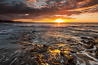 Red and yellow colors highlight a brilliant sunset and rushing water at Puako Bay, Big Island.