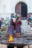 Chichicastenango, Guatemala.  Fire Burns on the Steps Leading to the Church of Santo Thomas, Sunday Morning.  Women of the Quiche (K'itche') Ethnic Group.