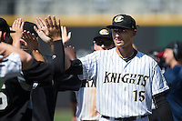 Trayce Thompson (15) of the Charlotte Knights high fives teammates as they celebrate their win over the Indianapolis Indians at BB&T BallPark on June 21, 2015 in Charlotte, North Carolina.  The Knights defeated the Indians 13-1.  (Brian Westerholt/Four Seam Images)