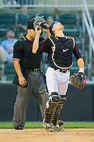 Zachary Fisher (13) of the Kannapolis Intimidators rips his mask off as he tracks a pop fly while home plate umpire Jorge Teran looks on during the South Atlantic League game against the Hagerstown Suns at CMC-Northeast Stadium on May 17, 2013 in Kannapolis, North Carolina.  The Suns defeated the Intimidators 9-7.   (Brian Westerholt/Four Seam Images)