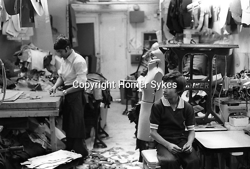 East End London Asian Sweat Shop. Asian boy in small clothing manufacturing factory, just off Brick Lane 1978