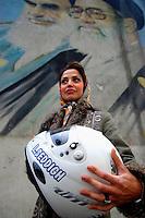 A portrait of Laleh Seddigh with her crash helmet below a billboard depicting Iran's Supreme Leader Ayatollah Ali Khamenei (right) and Ayatollah Khomeini (left). Seddigh is Iran's best female racing car driver.