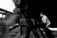 """Poland. Silesia. Chorsow. """" Hutta Kosciuszko """" is the factory's name. Metallurgist at work.Coal pile and coke burning. Major polluted area due to old iron and steel works and heavy metals supended in the air. Chorsow is a small town, distant 20 km from Katowice. © 1991 Didier Ruef"""