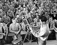 """Instructor M. Deskovitch, PhoM 1/c, giving a lecture on the 4""""x5"""" graphic view camera, to Class II students Advanced Ground Photography."""