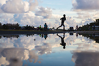 A boy runs next to a flooded area near the airport runway, in downtown Funafuti. Parts of the island flood at this time of the year due to the 'king tides'. The king tides are seasonal and are characterised by very high water levels in the surrounding ocean. At this time of year the waves inundate the coastline but also water seeps up through the ground which is made of porous coral. This natural phenomenon is particularly serious for Tuvalu, a low-lying atoll island nation, whose highest point is only a few metres above sea level. As sea levels rise, the king tides regularly flood parts of the island and will likely increase in severity in the future, potentially making large parts of the nation uninhabitable. Funafuti, Tuvalu. March, 2019.