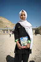 A school girl stands outside her school.
