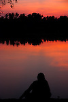 Silhouette of Woman at Sunset Looking Over Kerala Backwaters