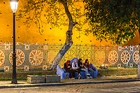 Chefchaouen, Morocco.  Women Talking on a bench, Place Outa El-Hammam, Night.