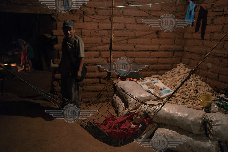 Bernardino Sanchez, founder of the Regional Coordinator of Community Authorities (CRAC-PF) police force, watches his youngest daughter sleeping at home in a hammock while his wife, Adelo Virgeno, prepares tortillas. Murders in Mexico rose to a new record in 2019, the first full year of Andres Manuel Lopez Obrador's presidency, posing a challenge to the popular leader to make good on a campaign promise of reducing violence. <br /><br />CRAC-PF was formed as a response by a cluster of remote farming villages, largely inhabited by indigeneous Nahuas indians, to the violent Los Adillos drug cartel who want to force the farmers to grow opium poppies. While elders admit that the training and arming of their children is really a ploy to get the attention of the central government who they say have failed to respond to their plight. Nonetheless, children cannot leave the villages defended by the CRAC-PF in order to attend secondary school and anyone caught by the brutal cartels is at risk of losing their life.