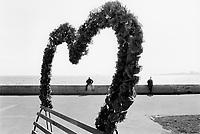 Azerbaijan. Baku Region. Baku. Town center. Caspian sea. Two muslim men, a wall, a bench and a heart made of fake plastic flowers on the Boulevard in the National Park. Heart-shaped floral arrangement.  © 2007 Didier Ruef