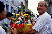 Salvador, Bahia, Brazil. Candomble follower carrying offering of flowers, combs, doll, etc.; Festival of Iemanja.