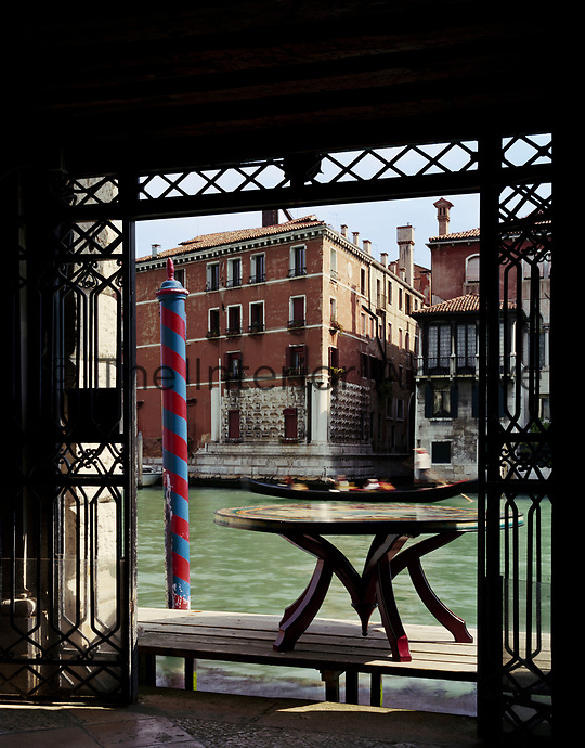 A gondola speeds past the terrace of Lars Rachen's Venetian apartment. His prized Fornasetti-topped dining table brought out into the light for its glory to be appreciated.