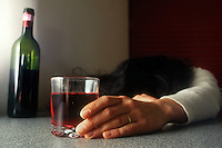 Donna alcolista beve un bicchiere di vino rosso..Woman drink a glass of red wine....