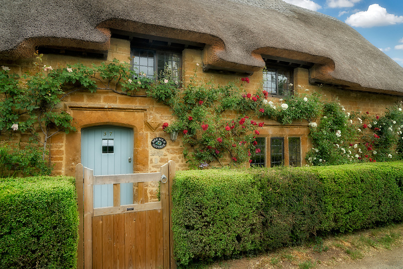 Thatched houses with roses in Great Tew, The Cotswolds, England