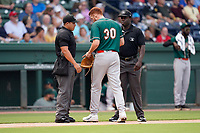 Starting pitcher Santiago Florez (30) of the Greensboro Grasshoppers has his glove and hat checked for sticky substances by umpires James Jean and Ray Valero in a game against the Greenville Drive on Thursday, July 22, 2021, at Fluor Field at the West End in Greenville, South Carolina. (Tom Priddy/Four Seam Images)