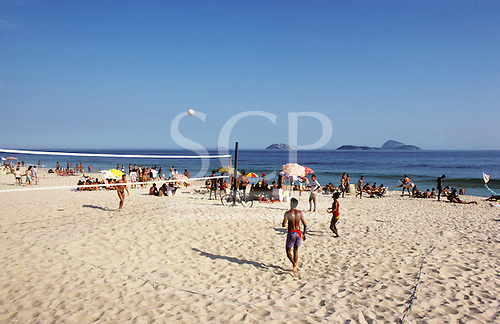 Rio de Janeiro, Brazil. Young people playing volleyball on Copacabana beach with sunhades behind.