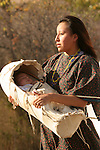 A young Native American Indian women with her baby in a baby cradle