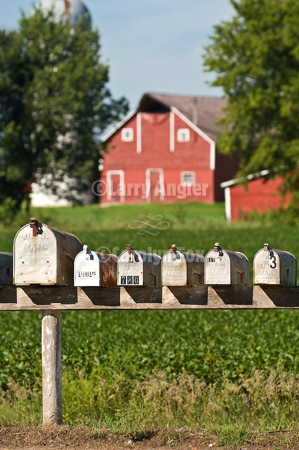 Mail boxes in row in from of a farm with red barn