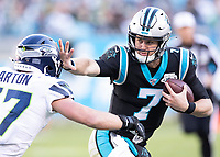 CHARLOTTE, NC - DECEMBER 15: Kyle Allen #7 of the Carolina Panthers runs with the ball and straight arms Cody Barton #57 of the Seattle Seahawks during a game between Seattle Seahawks and Carolina Panthers at Bank of America Stadium on December 15, 2019 in Charlotte, North Carolina.