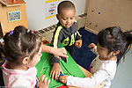 Eucation Preschool Head Start Early Learn 2s program two girls and a boy interacting over puzzle