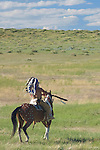 An Indian Chief on horseback and dressed in full regalia pauses for a moment against a vibrant Montana blue sky and appears to be paying homage to the spirit earth during the  performing of the reenactment of the annual Battle of the Little Bighorn in Hardin Montana. Model Release