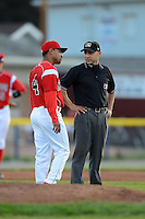 Batavia Muckdogs manager Angel Espada #4 argues a call with umpire Derek Moccia during a game against the Mahoning Valley Scrappers on June 21, 2013 at Dwyer Stadium in Batavia, New York.  Batavia defeated Mahoning Valley 3-2.  (Mike Janes/Four Seam Images)