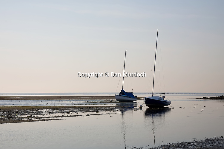 Two small sailboats aground at low tide