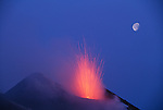 The moon hovers a safe distance from exploding magma, Stromboli, Italy