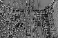 An extreme black and white view looking up through the cables at the Brooklyn Bridge in NYC.