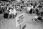 Blackpool Beach Lancashire Uk. 1970s. Holidaymakers sun themselves crowded beach. Keep this Space Clear. A safty warning sign...