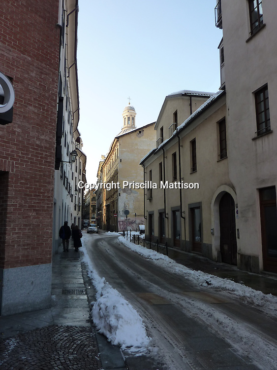 Turin, Italy - February 3, 2012:  The late afternoon sun still lights part of a snowy street.