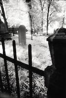 Gravestone behind fence..