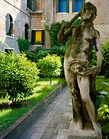 A tranquil courtyard garden is enclosed by gothic brick buildings and features a series of statues overgrown with moss