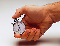 Hand holding a stop watch.