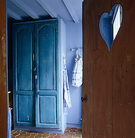 Antique French doors with original paint are reused to make a larder in the old kitchen of this 19th-century Normandy coaching inn