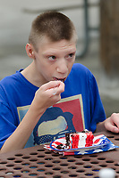 "Michael McCollum<br /> 8/2/18<br /> Ryan tries out the cake at the reveal ceremony where it was announced to 13 year old Ryan Overman of west Knoxville that The Wish Connection is granting Ryan's wish to go to Washington DC and visit the White House at Carl Cowan Park, 10058 S Northshore Dr, Knoxville, TN , Thursday, August 2, 2018 at 5:45pm. Approximately 50-60 people attended, including the Overman family, friends, and AT&T Employees. The Bearden High School Cadets also attended and lead the pledge of allegiance.<br />  The AT&T Wish Connection is going to send Ryan, his family, and his service dog to Washington DC and while they are gone, the group of volunteers will be doing a makeover on his bedroom and turn it into the ""Oval Office"" at the White House.<br /> Ryan was born two weeks prematurely on May 13, 2005.  During the pregnancy he was classified as high risk due to a measured lack of growth and, after a brief stay in the hospital, he came home weighing only 4 lbs 5 oz.  His development was much slower compared to his peers, such as not learning to walk until he was well over a year old, and he was much smaller. The Overman family worked with Tennessee Early Intervention Services (TEIS) when Ryan was about one year old and with their help they were able to get Ryan enrolled through TEIS to receive Occupational, Physical, and Speech Therapy.  When Ryan turned three he transitioned from TEIS to the Knox County Early Intervention Program and began attending a special school to continue his therapies until he was old enough to enroll at Cedar Bluff Elementary and now is at Cedar Bluff Middle School. In 2016, Ryan was diagnosed to have retinitis pigmentosa, a degenerative disease of the retinas that under the best of circumstances causes severe tunnel vision, but more commonly results in complete blindness.<br />  Despite the physical difficulties that Ryan has had to endure over the last thirteen years, he continually brightens the lives of those around him.  If someone is hurting"