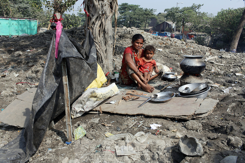 A woman and child, who are refugees from Bangladesh, sit on the banks of a canal in the Rajabazar district of central Kolkata. The government has recently cleared the banks of the nearby canal in an attempt to clean up the waterway. India. November, 2013