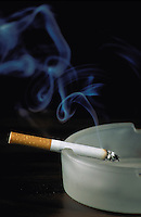 A cigarette smoking in an ashtray. Tobacco, Health, Addictions.