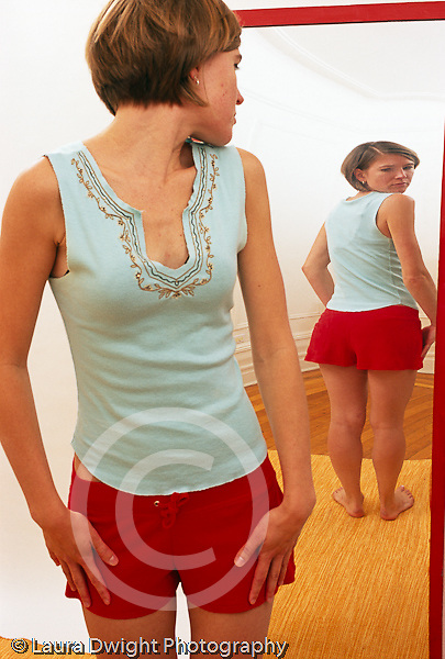 illustration of body image and societal distortions and expectations slender young woman viewing herself in a fun house distorting mirror vertical