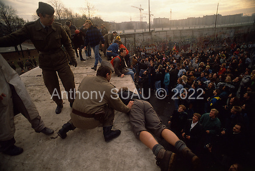 West Berlin, West Germany<br /> November 11, 1989<br /> <br /> East German police mount the wall and push protesters off at the Brandenburg Gate November 11, 1989 in Berlin, Germany. The East German government lifts travel and emigration restrictions to the West on November 9, 1989.
