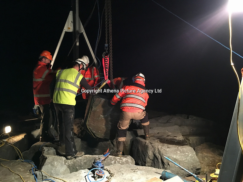 Pictured: A boulder is lifter as part of the seal pup rescue operation in Aberavon beach, Port Talbot, Wales, UK. Tuesday 07 November 2017<br /> Re: A baby seal was rescued from under a one ton rock after being frightened by fireworks.<br /> The pup - nicknamed Miracle - wriggled into a gap between rocks and was unable to get out.<br /> Surfers heard the pup crying and a huge rescue operation was launched at Aberavon Beach, Port Talbot, South Wales.<br /> An RNLI lifeboat crew tried to pull the seal to safety but it was stuck and out of reach.