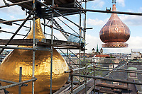Switzerland. Geneva.The Russian Church (full name: Cathédrale de l'Exaltation de la Sainte Croix) is designed in a Byzantine Moscovite style. The church is a lovely 19th-century Russian Orthodox church topped with golden onion domes. The roof and all onion domes undergo a complete revival restoration by the roofing company « Cerutti Toitures SA ». A newly restored copper bulb (R) is carried by a crane while the old central golden bulb (L) will soon be dismantled. The newly restored copper bulb (R) will later be painted in yellow and gilded with golden leaves. The Russian church serves today not only the Russian community but also Bulgarians, Serbs, Coptic Christians and other Orthodox worshippers who do not have their own church in Geneva. In the background, the St.Pierre Cathedral of the Reformed Protestant Church. An onion dome is a dome whose shape resembles an onion. Such domes are often larger in diameter than the drum upon which they sit, and their height usually exceeds their width. These bulbous structures taper smoothly to a point. 25.04.2016 © 2016 Didier Ruef