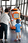 """August 01 2012, Tokyo, Japan - Visitors see the new robot guide """"Tawabo"""" at vantage point of Tokyo Tower. Tokyo Tower implemented the new robot guide which name is """"Tawabo"""", the first indoor robot guide in Japan. It can speak Japanese, English, Chinese and Korean, it weights 200kg and it is 160cm tall."""